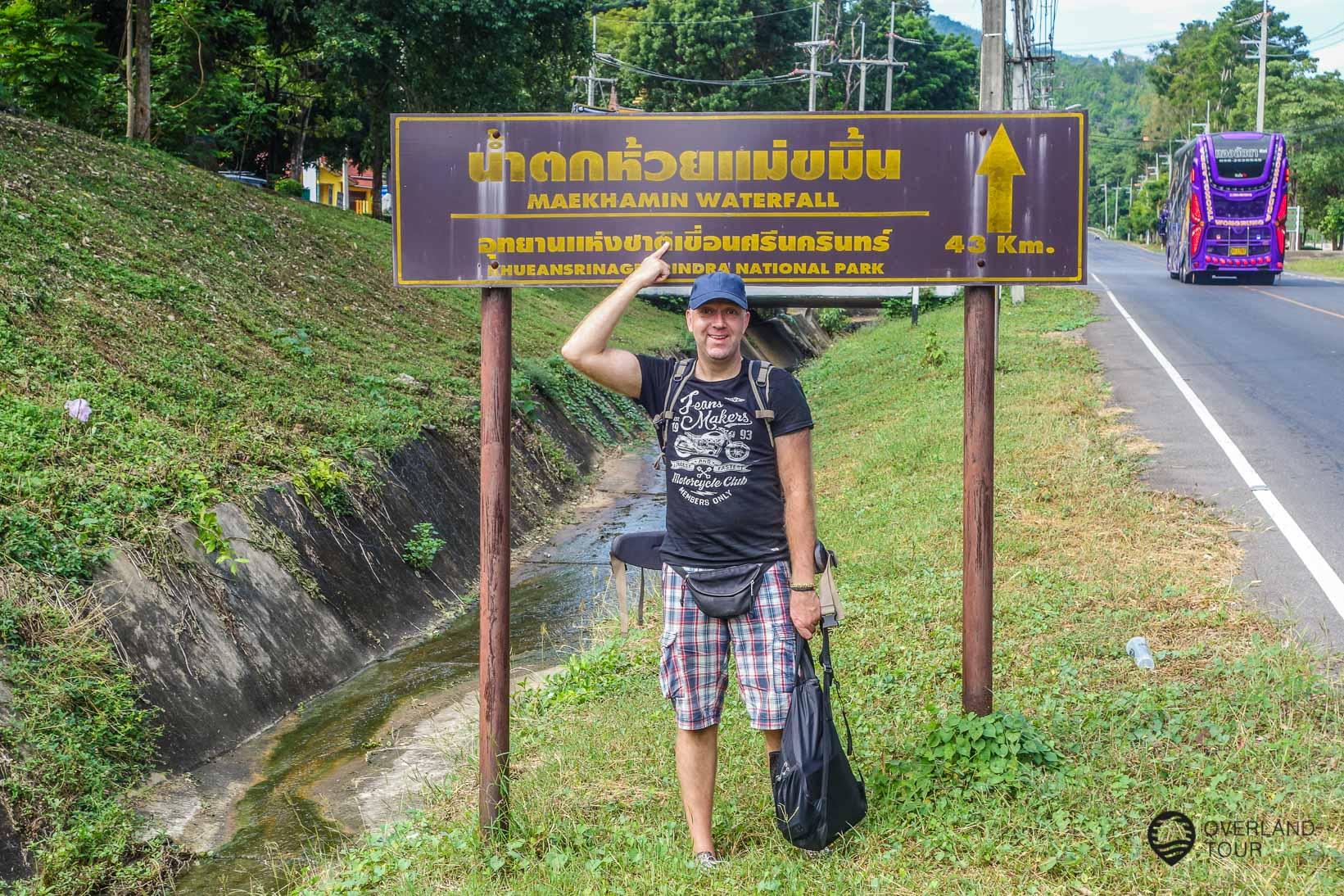 An der Hauptstraße und der Einfahrt der Erawan Wasserfällen. Weiter geht es noch zu den Huay Meakamin Waterfalls - Nur noch 43 km per Anhalter