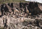 Der Panoramablick vom geschotterten Parkplatz am des Ufer des Mtkwari auf das Höhlenkloster Wardsia
